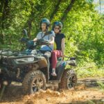 two people driving a quad vehicle through mud and water