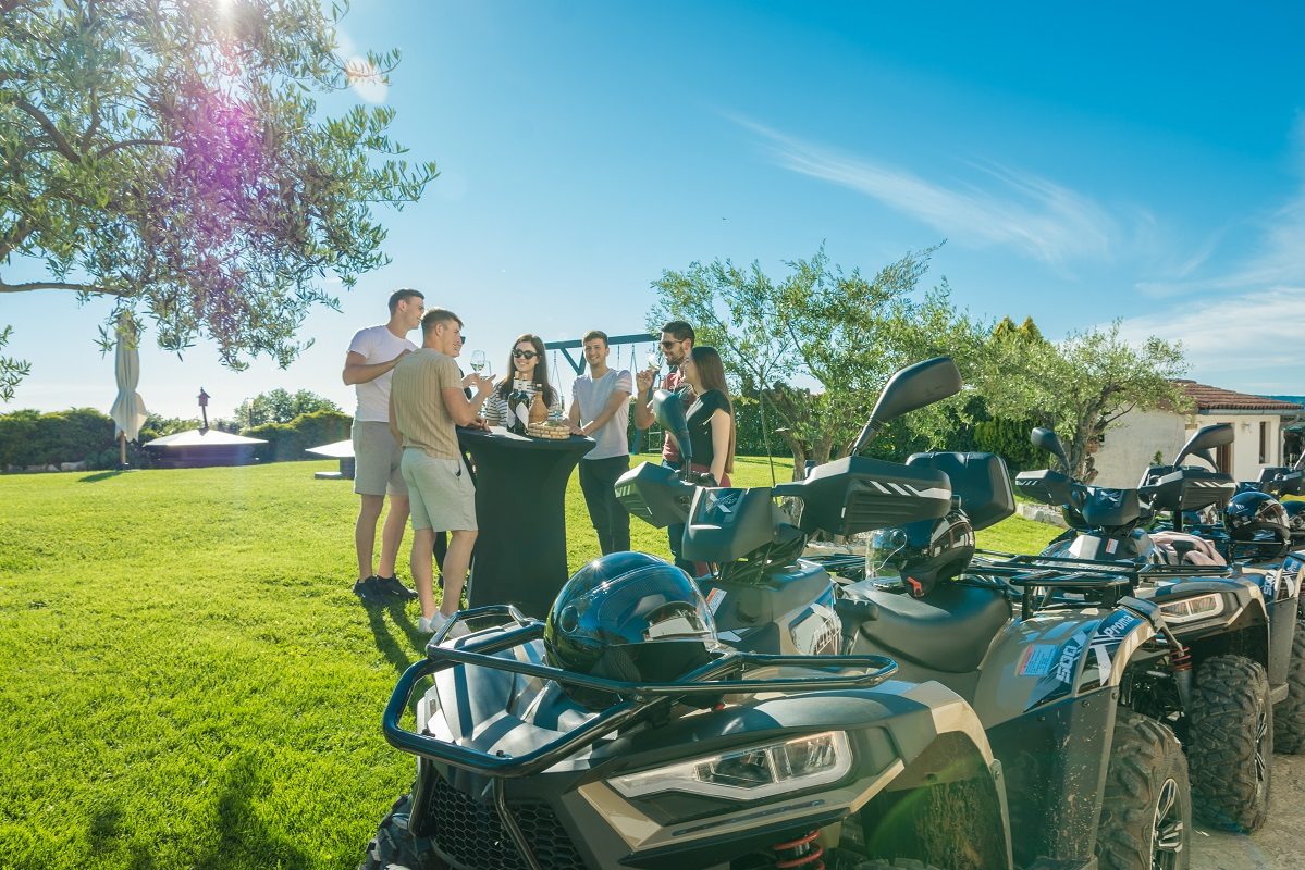 atv vehicle and people tasting vine in the background