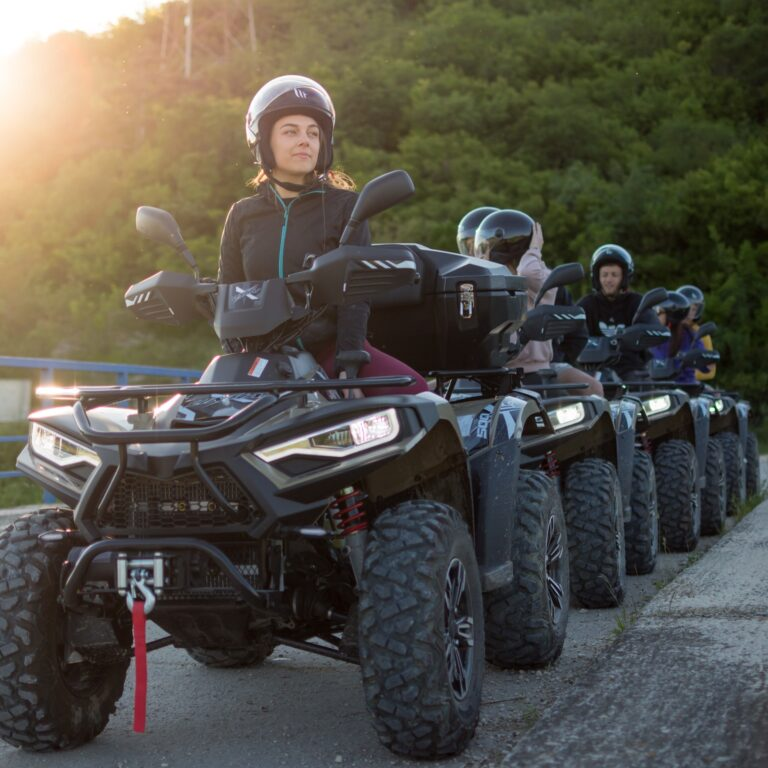 people driving quad vehicles on the bridge crossing a river