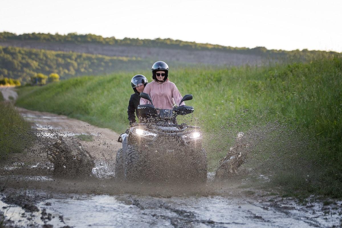 people driving a quad trough puddle